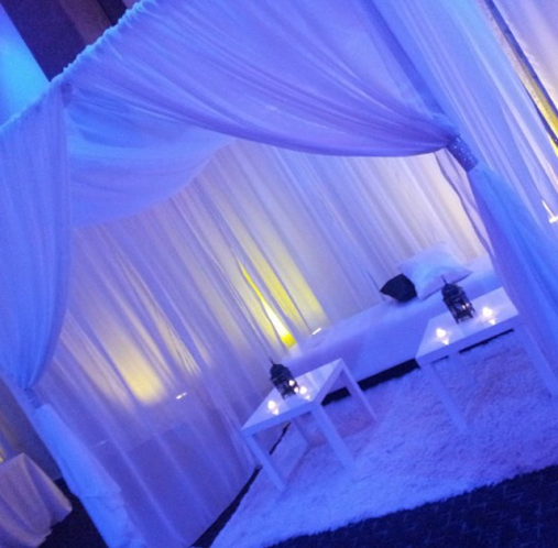 [Image: Sheer curtains for draping seating area featuring up-lights and candles to lighten up the mood. ]