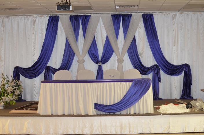 [Image: Purple and white drapery for the bride and groom table.]