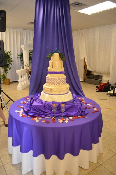 This gorgeous wedding cake table features beautiful purple and white accents to match the cake. The drapery behind the cake makes it stand out even more!