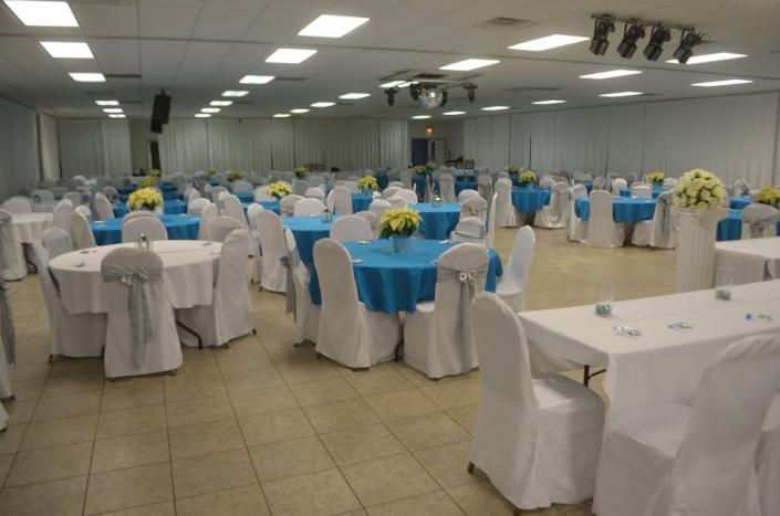 This blue and white themed reception features blue and white table linens and white chair covers accented with silver chair sashes.